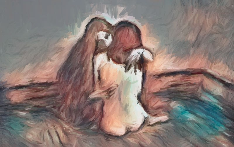 Two women on bare floor embracing.